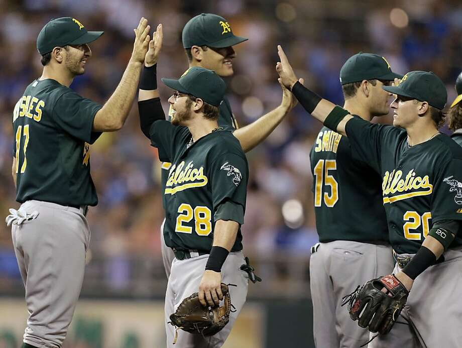 Oakland Athletics celebrate after their baseball game against the Kansas City Royals, Friday, July 5, 2013, in Kansas City, Mo. The Athletics won the game 6-3. (AP Photo/Charlie Riedel) Photo: Charlie Riedel, Associated Press