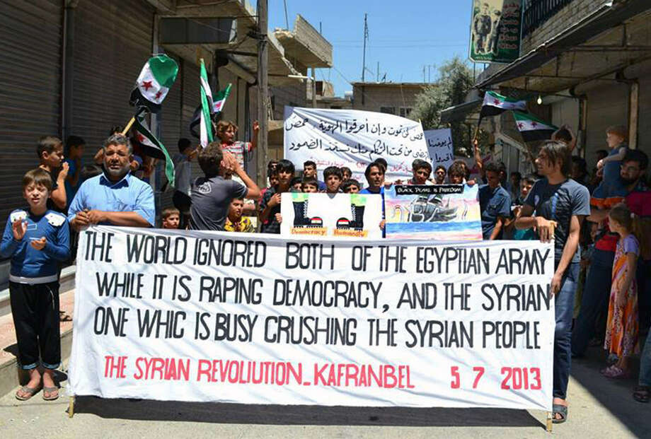 Protesters with banners and revolution flags in northern Syria urge the international community to take action to protect them from government attacks. Photo: Edlib News Network / Associated Press