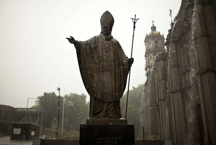 A statue of Pope John Paul II stands outside the Basilica of Guadalupe during heavy rain in Mexico City, Friday, July 5, 2013. Pope Francis on Friday approved the miracle of a Costa Rican woman bringing John Paul to the ranks of saints. Floribeth Mora suffering from a cerebral aneurysm and only given a month to live, was inexplicably cured on May 1, 2011, the date of John Paul's beatification, when millions of worshippers filled St. Peter's Square to honor the beloved Polish pontiff. (AP Photo/Ivan Pierre Aguirre) Photo: Ivan Pierre Aguirre, Associated Press