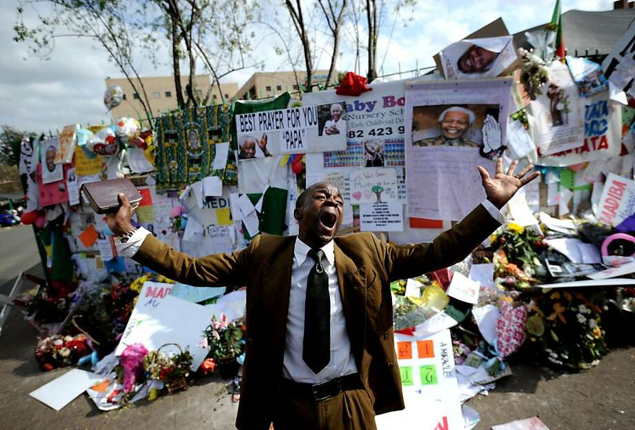 """A preacher gives a speech on July 5, 2013 outside the Medi Clinic Heart Hospital where former South African President Nelson Mandela is hospitalized in Pretoria. During a nearly one month battle for his life in hospital, ailing South African icon Nelson Mandela has occasionally been uncomfortable but has not been in pain, his wife Graca Machel said on July 4. Doctors treating Nelson Mandela said he was in a """"permanent vegetative state"""" and advised his family to turn off his life support machine, according to court documents dated June 26, obtained by AFP. AFP PHOTO / STEPHANE DE SAKUTINSTEPHANE DE SAKUTIN/AFP/Getty Images Photo: Stephane De Sakutin, AFP/Getty Images"""