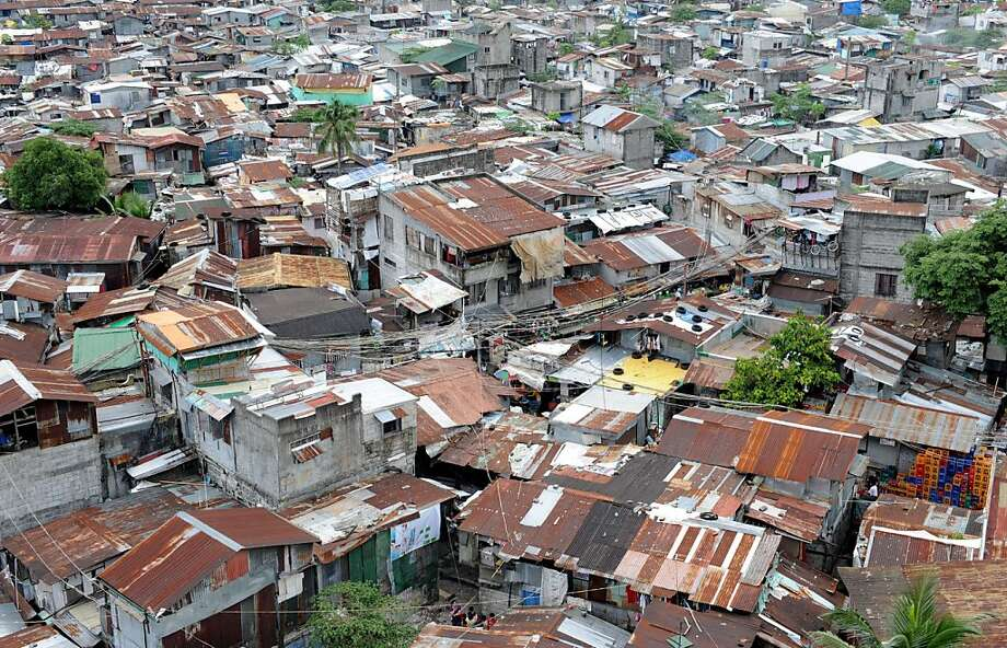 A general view shows a large slum area in a suburb of Manila on July 5, 2013. The Philippines said on July 5 it was aiming to lift more than 10 million people out of poverty in less than two years, and make an enduring impact on lessening one of Asia's worst rich-poor divides. The government has set a target of cutting the number of people living in poverty to 16.6 percent by the end of 2015, down from 27.9 percent last year, Socio-Economic Planning Secretary Arsenio Balisacan said.  AFP PHOTO / Jay DIRECTOJAY DIRECTO/AFP/Getty Images Photo: Jay Directo, AFP/Getty Images