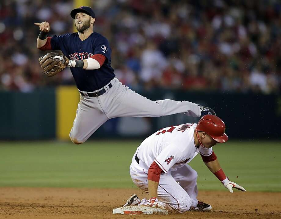 Boston Red Sox's Dustin Pedroia, top, throws to first base to complete a double play after forcing out Los Angeles Angels' Mike Trout, bottom, during the third inning of a baseball game in Anaheim, Calif., Friday, July 5, 2013. Angels' Albert Pujols was out at first. (AP Photo/Jae C. Hong) Photo: Jae C. Hong, Associated Press