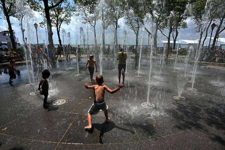 Children play in a fountain in Battery Park July 5, 2013 in New York's Lower Manhattan as hot and humid weather settles into the northeast. Temperatures were reported at 98 Fahrenheit (36.6 C). AFP PHOTO/Stan HONDASTAN HONDA/AFP/Getty Images Photo: Stan Honda, AFP/Getty Images