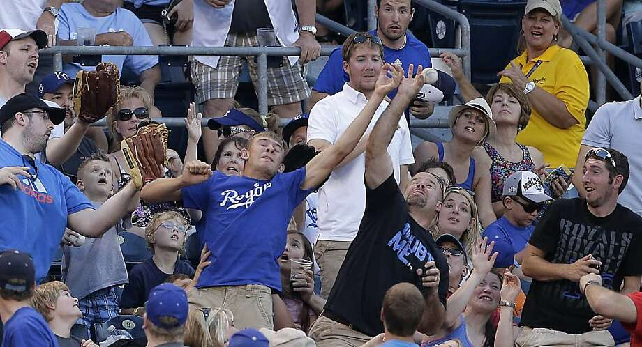Fans try to catch a fly foul ball hit by Oakland Athletics' Seth Smith during the fifth inning of a baseball game against the Kansas City Royals Friday, July 5, 2013, in Kansas City, Mo. (AP Photo/Charlie Riedel) Photo: Charlie Riedel, Associated Press