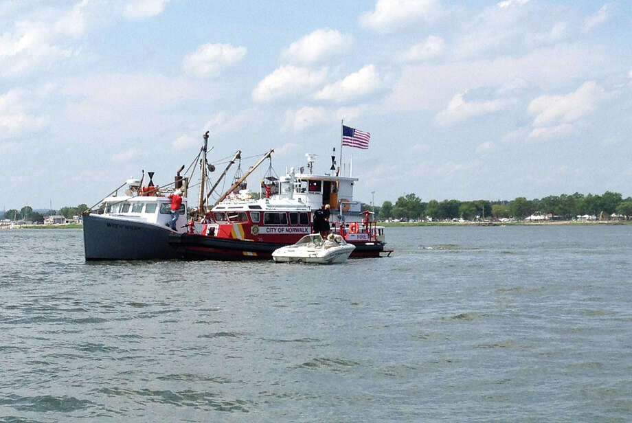Norwalk and Westport marine patrols assist a small boat that caught fire in Norwalk Harbor in Norwalk, Conn., on Saturday, July 6, 2013. Photo: Lindsay Perry / Stamford Advocate