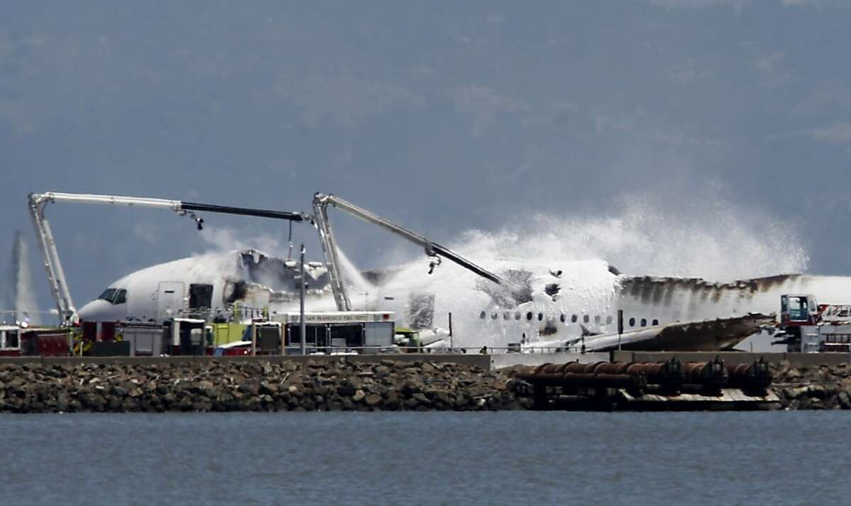 Fire crews pour water and foam on an Asiana Airlines Boeing 777 that crashed while it was attempting to land from Seoul, South Korea at San Francisco International Airport in San Francisco, Calif. on Saturday, July 6, 2013.