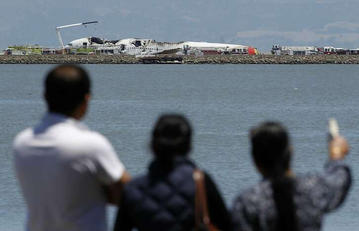 People view the wreckage of an Asiana Airlines Boeing 777 that crashed while it was attempting to land from Seoul, South Korea at San Francisco International Airport in San Francisco, Calif. on Saturday, July 6, 2013.
