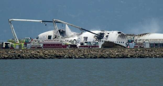 Fire crews pour water on the wreckage of an Asiana airliner at San Francisco International Airport Saturday. (AP photo by Noah Berger)