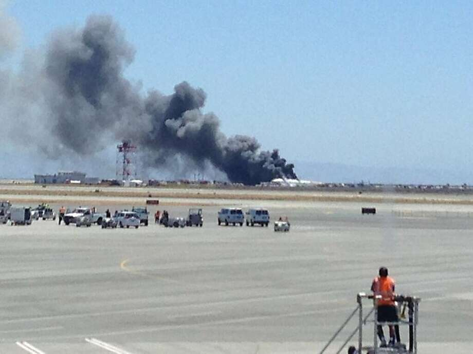 This photo provided by Krista Seiden shows smoke rising from what a federal aviation official says was an Asiana Airlines flight crashing while landing at San Francisco airport on Saturday, July 6, 2013. It was not immediately known whether there were any injuries. (AP Photo/Krista Seiden) Photo: Krista Seiden, Associated Press