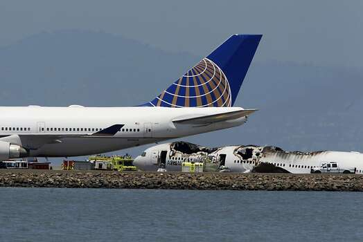 A United Airlines 747 that was waiting to takeoff is towed past the fuselage of an Asiana Airlines Boeing 777 that crashed while it was attempting to land at San Francisco International Airport in San Francisco, Calif. on Saturday, July 6, 2013. Photo: Paul Chinn, The Chronicle