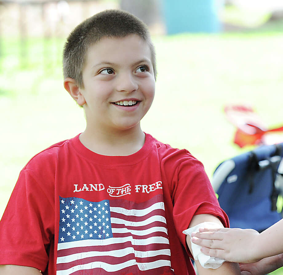 Paul Migliaccio, 8, of Greenwich, smiles while getting a temporary tattoo prior to the Town of Greenwich fireworks show at Binney Park in Old Greenwich, Saturday, July 6, 2013. Photo: Bob Luckey / Greenwich Time