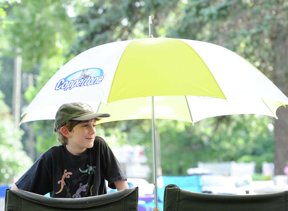 Zack DiBella, 11, of Greenwich, stays cool under an umbrella prior to the Town of Greenwich fireworks show at Binney Park in Old Greenwich, Saturday, July 6, 2013. Photo: Bob Luckey / Greenwich Time