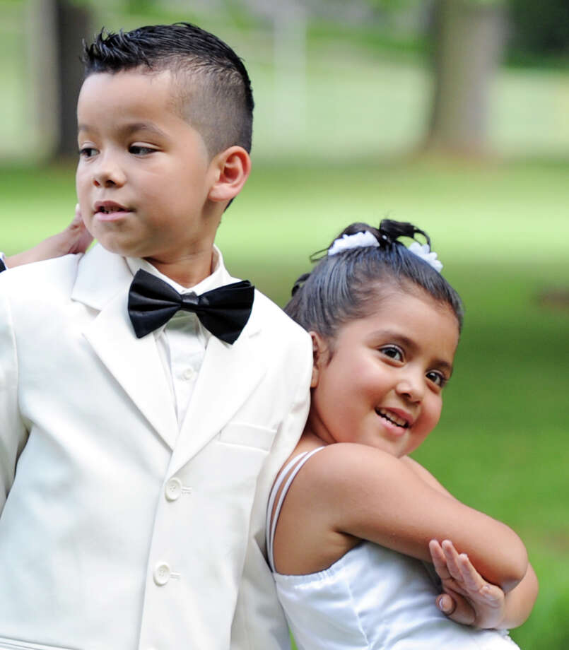 At left, Brandon Chauarria, 9, of Stamford, and his cousin, Madeline Diaz, 5, of Norwalk, pose during a wedding photo shoot prior to the Town of Greenwich fireworks show at Binney Park in Old Greenwich, Saturday, July 6, 2013. Photo: Bob Luckey / Greenwich Time