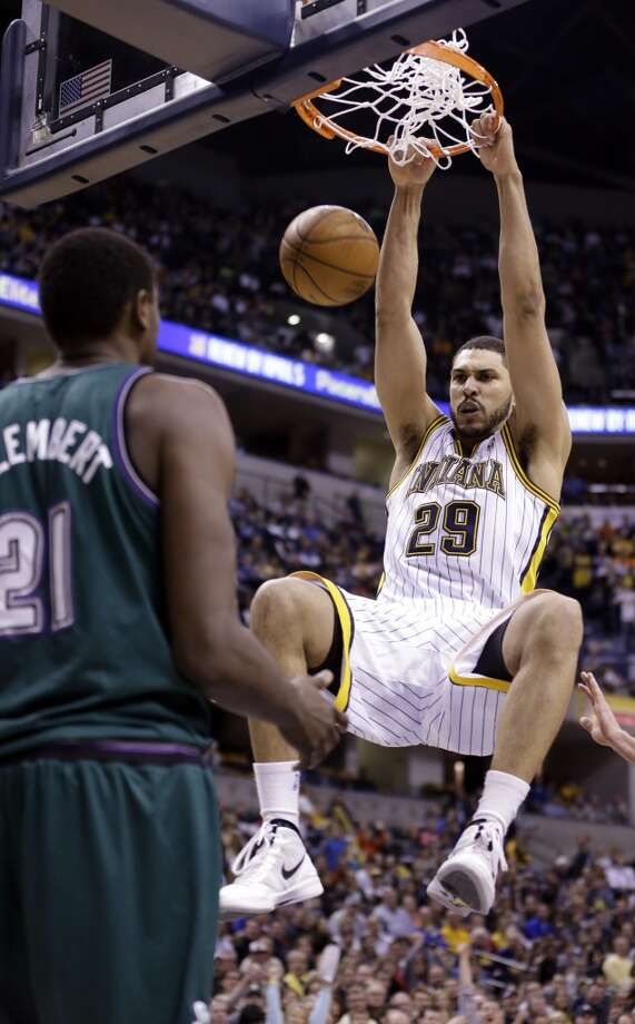 Indiana Pacers forward Jeff Pendergraph (29) hangs on the rim after a dunk over Milwaukee Bucks center Samuel Dalembert in the second half of an NBA basketball game in Indianapolis, Friday, March 22, 2013. The Pacers defeated the Bucks 102-78. (Michael Conroy / Associated Press)