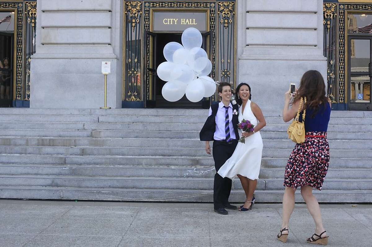Lisa Dazols, 34, and Jenni Chang, 31, stop for a final photograph outside San Francisco City Hall after getting officially married on Tuesday July 2, 2013.