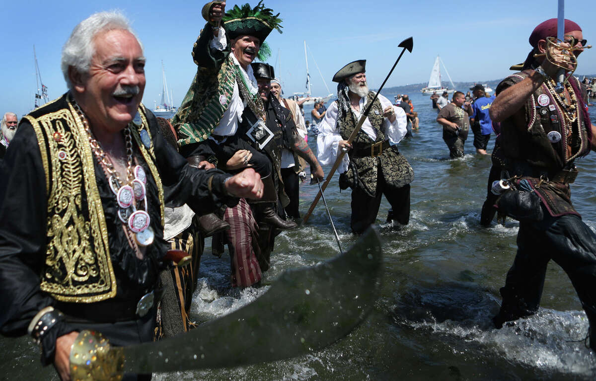 Seafair Pirates march onto shore on Saturday, July 6, 2013 at Alki Beach in West Seattle. Thousands came out to see the annual landing of the pirates, a much-loved Seafair tradition.