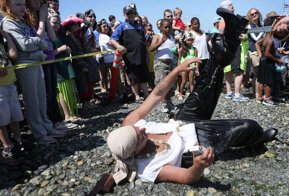 A Seafair Pirate empties water out of his boot after marching onto shore on Saturday, July 6, 2013 at Alki Beach