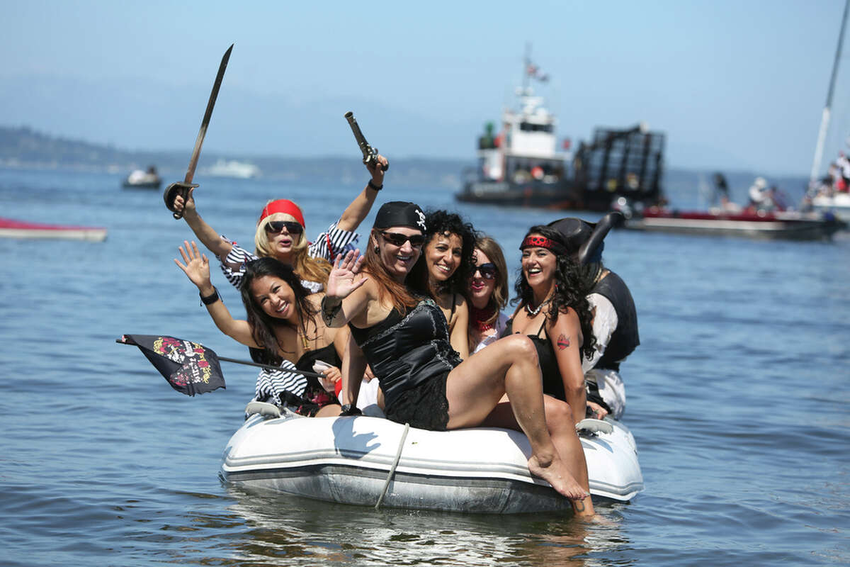 Female pirates pack into a dinghy as the Seafair Pirates march onto shore on Saturday, July 6, 2013 at Alki Beach in West Seattle.
