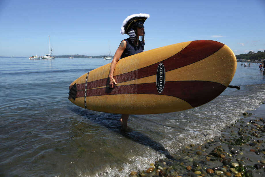 Sara May holds her paddle board after making her own landing during the annual Seafair Pirates landing. Photo: JOSHUA TRUJILLO, SEATTLEPI.COM