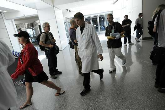 Doctors exiting the Reflection Room at San Francisco International Airport where passengers and families are being held after the Asiana Airlines plane crash on July 6, 2013. Photo: Michael Short, Special To The Chronicle