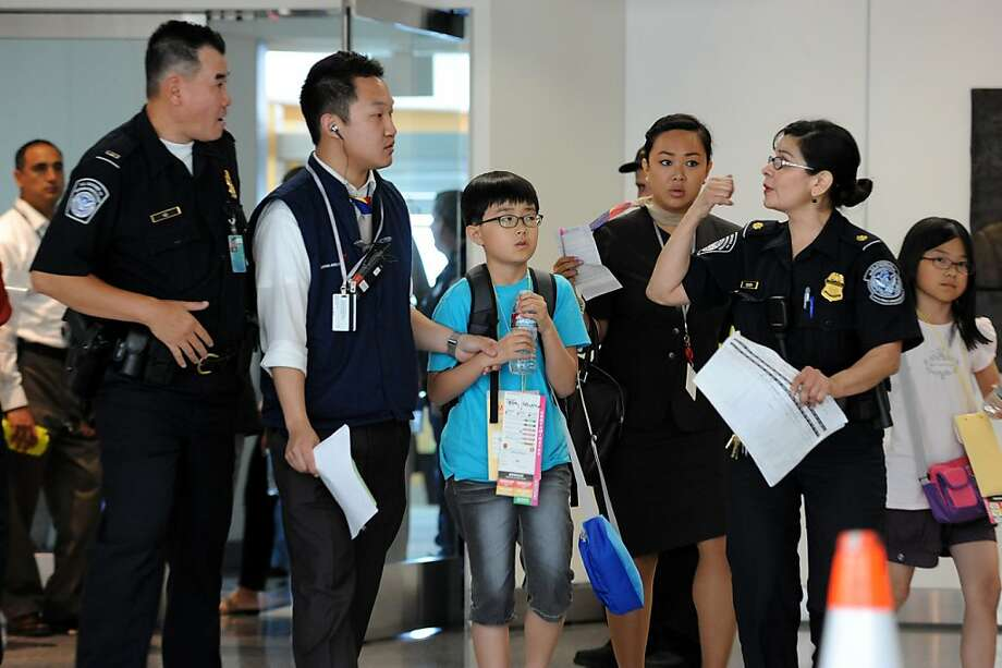 A young passenger from the Asiana Airlines Boeing 777 which crashed while it was attempting to land at San Francisco International Airport is escorted out of the Reflection Room in San Francisco International Airport where flight passengers are being held on July 6, 2013. Photo: Michael Short, Special To The Chronicle