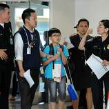 A young passenger from the Asiana Airlines Boeing 777 which crashed while it was attempting to land at San Francisco International Airport is escorted out of the Reflection Room in San Francisco International Airport where flight passengers are being held on July 6, 2013.