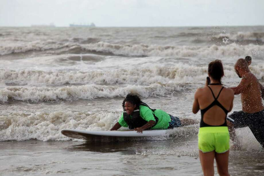 Participant Echante Guillory surfs into shore as Ohana Surf & Skate, partnered with the Wounded Warriors Project to host disabled veterans as they learned to surf at 28th & Seawall Saturday, July 6, 2013 in Galveston, Texas. Photo: Eric Kayne / ©2013 Eric Kayne