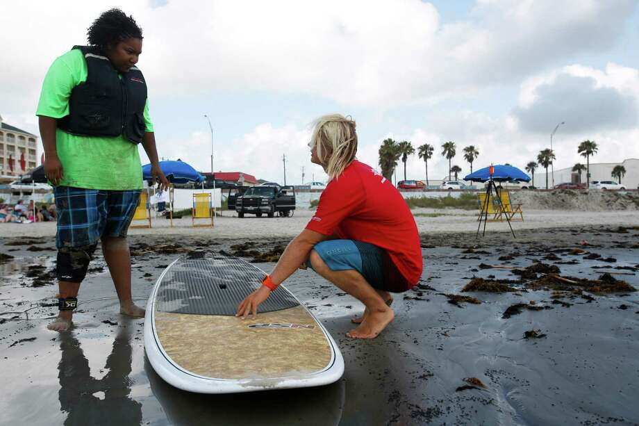 Echante Guillory, left, listens as instructor Connor Eck teaches her about surfing as Ohana Surf & Skate, partnered with the Wounded Warriors Project to host disabled veterans as they learned to surf at 28th & Seawall Saturday, July 6, 2013 in Galveston, Texas. Photo: Eric Kayne / ©2013 Eric Kayne