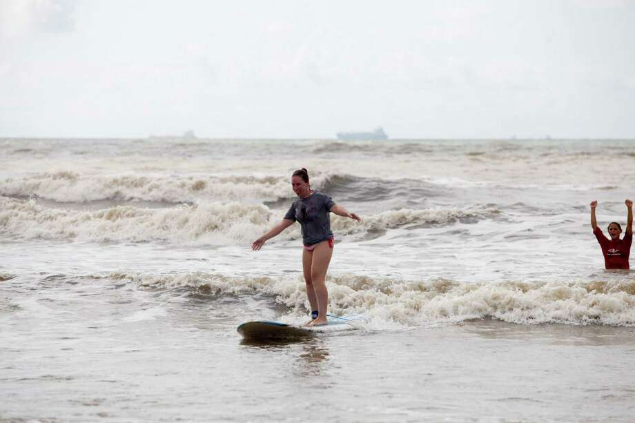 Participant Tammie Harris surfs into shore as Ohana Surf & Skate, partnered with the Wounded Warriors Project to host disabled veterans as they learned to surf at 28th & Seawall Saturday, July 6, 2013 in Galveston, Texas. Photo: Eric Kayne / ©2013 Eric Kayne