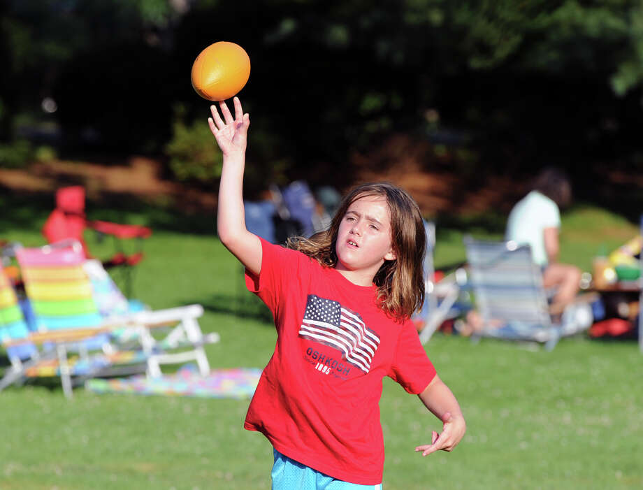 Lauren Steele, 7, of Old Greenwich, throws a sponge football prior to the Town of Greenwich fireworks show at Binney Park in Old Greenwich, Saturday, July 6, 2013. Photo: Bob Luckey / Greenwich Time