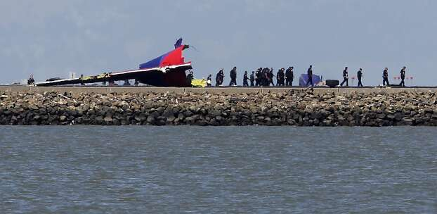 A team of emergency responders walk on the runway past the tail of an Asiana Airlines Boeing 777 that crashed while attempting to land at San Francisco International Airport in San Francisco, Calif. on Saturday, July 6, 2013. Photo: Paul Chinn, The Chronicle