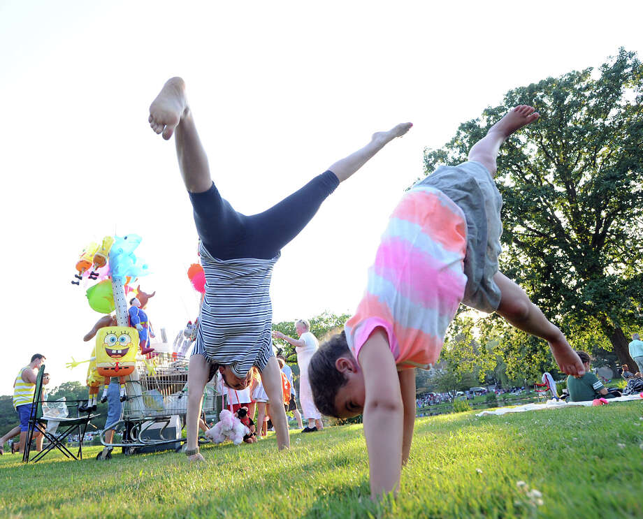 At left, Noa Eisenberg of Rowayton teaches how to do a cartwheel to Rowan Yomtov, 5, of Stamford, prior to the Town of Greenwich fireworks show at Binney Park in Old Greenwich, Saturday, July 6, 2013. Photo: Bob Luckey / Greenwich Time