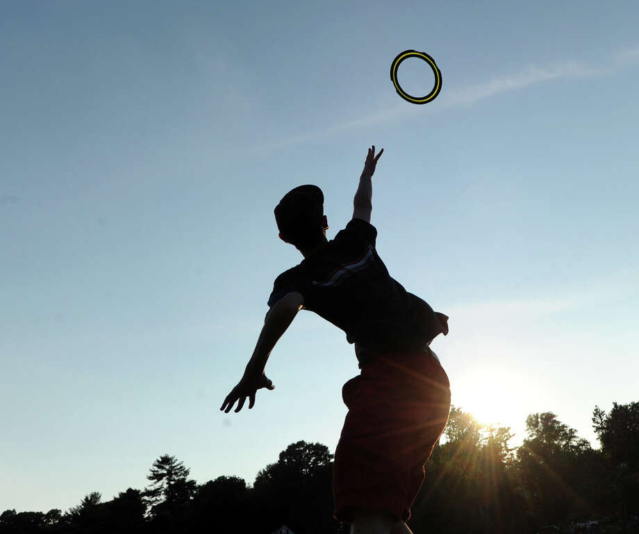 Andrew Clark, 14, of Weston, catches a flying disc prior to the Town of Greenwich fireworks show at Binney Park in Old Greenwich, Saturday, July 6, 2013. Photo: Bob Luckey / Greenwich Time
