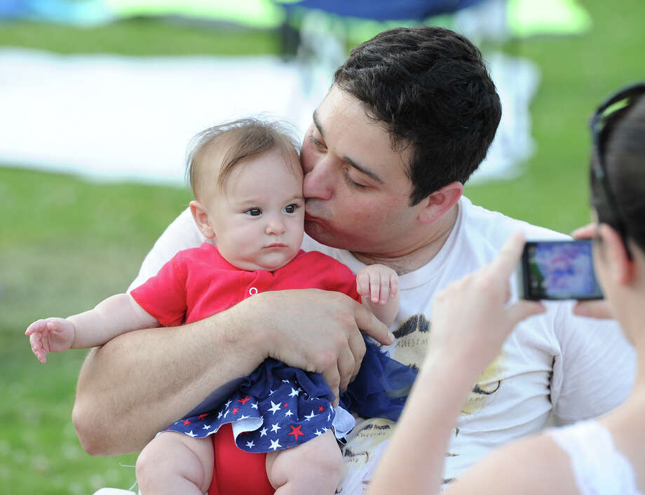 Mike Parisi of Greenwich gives a kiss to his daughter, Layla, 5 months, as his wife, Laurie, makes a photo prior to the Town of Greenwich fireworks show at Binney Park in Old Greenwich, Saturday, July 6, 2013. Photo: Bob Luckey / Greenwich Time