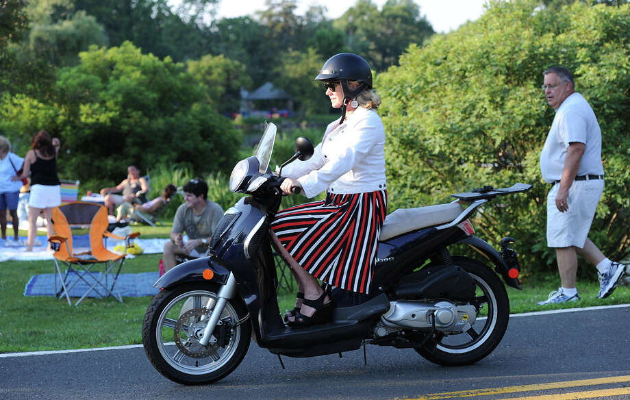 A woman wearing a red, white and blue skirt drives a motor scooter past Binney Park prior to the Town of Greenwich fireworks show at Binney Park in Old Greenwich, Saturday, July 6, 2013. Photo: Bob Luckey / Greenwich Time