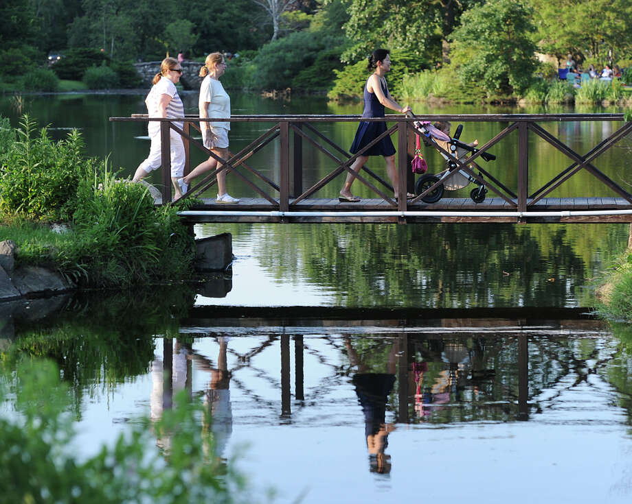 Pedestrians cross a bridge over Binney Park Pond prior to the Town of Greenwich fireworks show at Binney Park in Old Greenwich, Saturday, July 6, 2013. Photo: Bob Luckey / Greenwich Time
