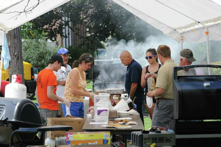 Members of the not-for-profit organization H.C. Smith Benefit Club of St. Johnsville cook hamburgers and hot dogs for volunteers and people in need after a recent flood in Fort Plain on Friday, July 5, 2013 in Fort Plain, N.Y. (Lori Van Buren / Times Union) Photo: Lori Van Buren / 00023067A