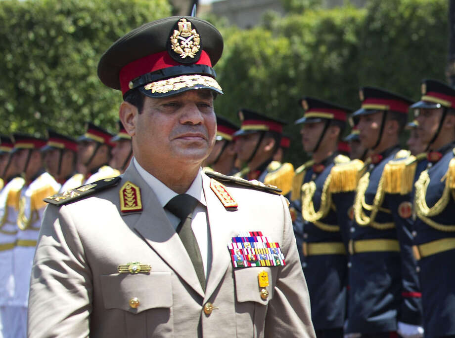 FILE - In this Wednesday, April 24, 2013 file photo, Egyptian Defense Minister Gen. Abdel-Fattah el-Sissi reviews honor guards during an arrival ceremony for his U.S. counterpart at the Ministry of Defense in Cairo. El-Sissi, born in 1954, appointed commander in chief of the Egyptian armed forces since August 2012, replacing Field Marshall Mohammed Hussein Tantawi. He is the chairman of the supreme council of the armed forces and the minister of defense. El-Sisi graduated from Egyptian military academy in 1977 and had masters degree from US army War College in 2006. He was appointed Commander of the Northern Military Region-Alexandria and then Head of Military Intelligence. (AP Photo/Jim Watson, Pool) Photo: Jim Watson, POOL / AFP Pool