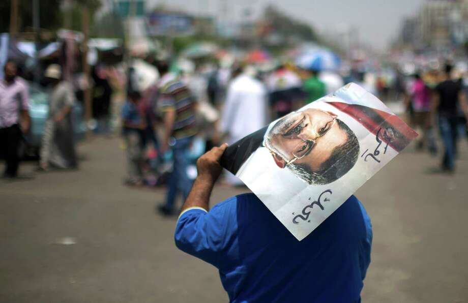 An Egyptian supporter of the Muslim Brotherhood holds a poster featuring deposed president Mohamed Morsi during a rally to support him on Saturday outside Cairo's Rabaa al-Adawiya mosque. Photo: MAHMUD HAMS, Staff / AFP