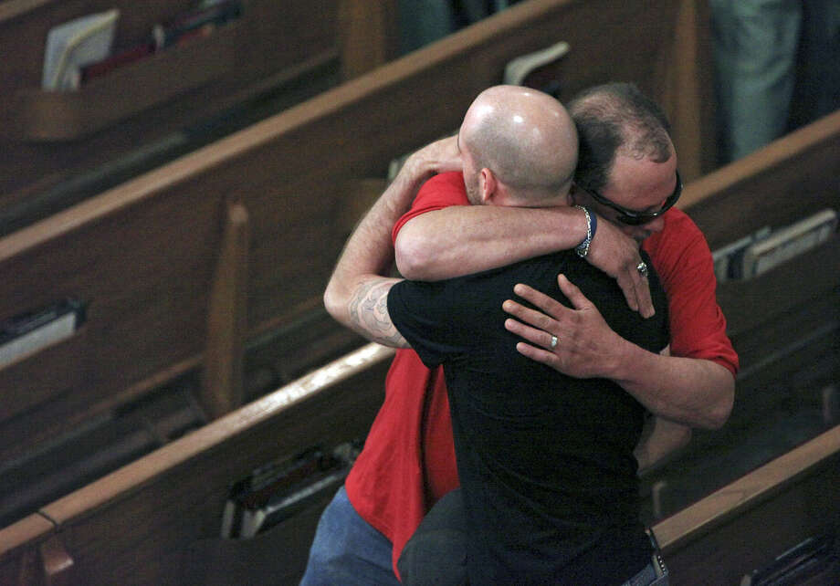 Jeff Clark (facing camera) comforts Dustin Matus after a Mass in West. Dustin's father,  Jimmy Matus was killed in the explosion. Photo: Edward A. Ornelas, San Antonio Express-News