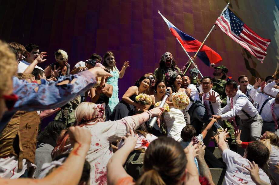 A wedding party outside of the Experience Music Project is overwhelmed by a flesh-hungry horde during the fifth annual Red, White and Dead Zombie Walk Saturday, July 6, 2013, around the Seattle Center in Seattle. This year, the horde relocated from their long-time Fremont location to the larger Seattle Center to accommodate more roaming, undead bodies. Photo: JORDAN STEAD, SEATTLEPI.COM / SEATTLEPI.COM