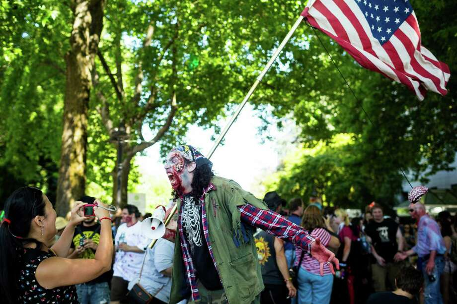 The zombie leader and other human-hungry walkers leave the Next 50 Plaza at the beginning of the fifth annual Red, White and Dead Zombie Walk Saturday, July 6, 2013, around the Seattle Center in Seattle. This year, the horde relocated from their long-time Fremont location to the larger Seattle Center to accommodate more roaming, undead bodies. Photo: JORDAN STEAD, SEATTLEPI.COM / SEATTLEPI.COM