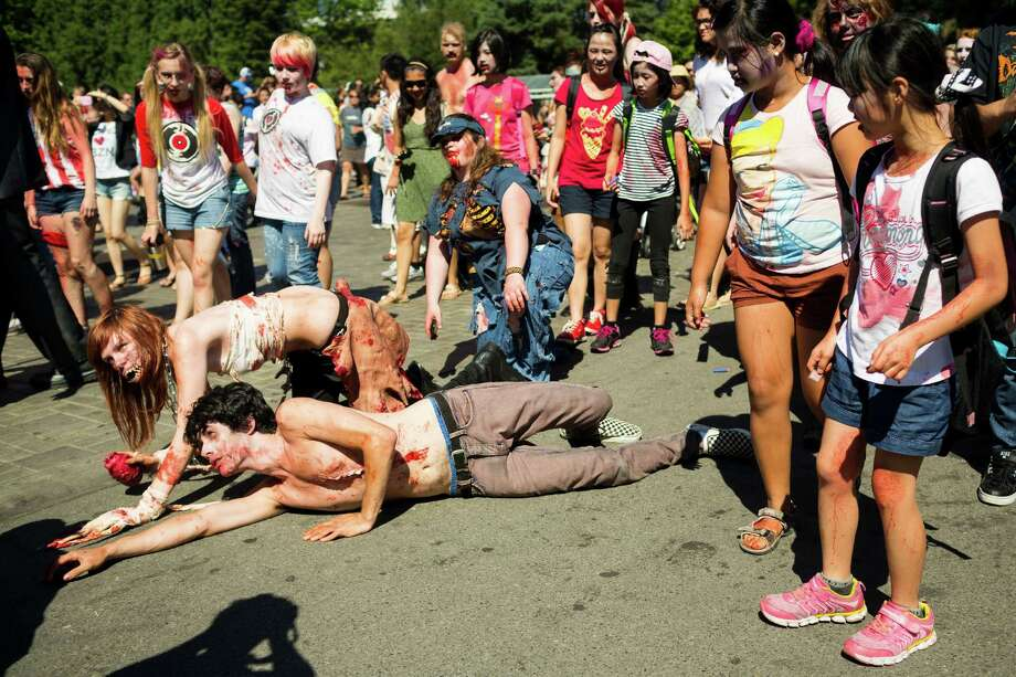 After suffering Nerf bullets by survivors, wounded zombies drag themselves by the International Fountain during the fifth annual Red, White and Dead Zombie Walk Saturday, July 6, 2013, around the Seattle Center in Seattle. This year, the horde relocated from their long-time Fremont location to the larger Seattle Center to accommodate more roaming, undead bodies. Photo: JORDAN STEAD, SEATTLEPI.COM / SEATTLEPI.COM