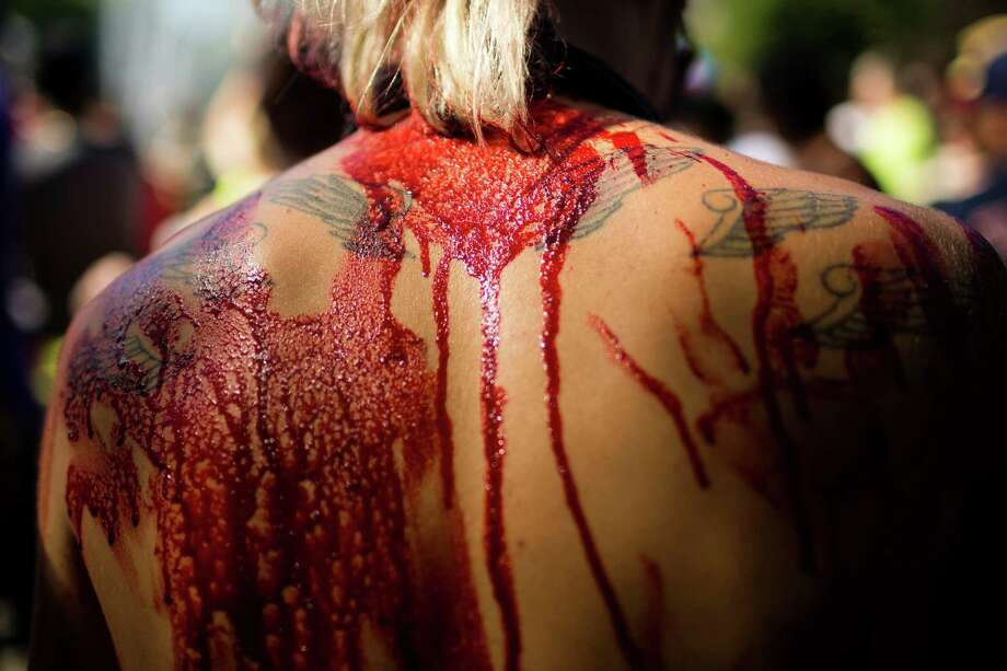 Fresh - and fake - blood stands out on sun-dappled, tattooed skin during the fifth annual Red, White and Dead Zombie Walk Saturday, July 6, 2013, around the Seattle Center in Seattle. This year, the horde relocated from their long-time Fremont location to the larger Seattle Center to accommodate more roaming, undead bodies. Photo: JORDAN STEAD, SEATTLEPI.COM / SEATTLEPI.COM