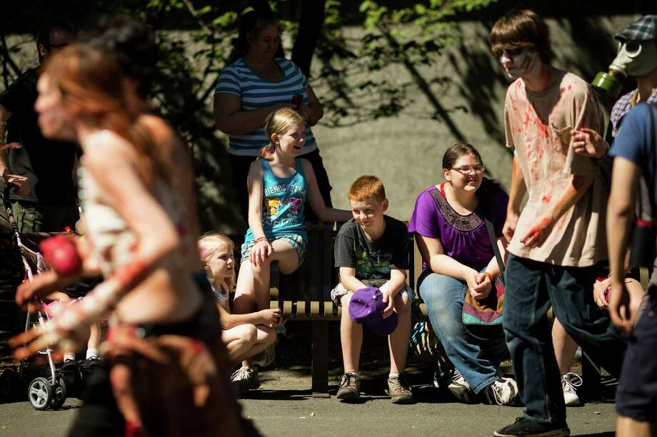 Onlookers take in the sights of the shambling undead during the fifth annual Red, White and Dead Zombie Walk Saturday, July 6, 2013, around the Seattle Center in Seattle. This year, the horde relocated from their long-time Fremont location to the larger Seattle Center to accommodate more roaming, undead bodies. Photo: JORDAN STEAD, SEATTLEPI.COM / SEATTLEPI.COM