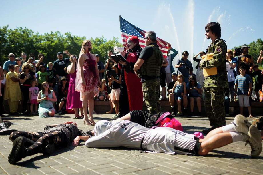 John, center right, and Tiffany O'Brien, center left, make real wedding vows during the fifth annual Red, White and Dead Zombie Walk Saturday, July 6, 2013, around the Seattle Center in Seattle. This year, the horde relocated from their long-time Fremont location to the larger Seattle Center to accommodate more roaming, undead bodies. Photo: JORDAN STEAD, SEATTLEPI.COM / SEATTLEPI.COM