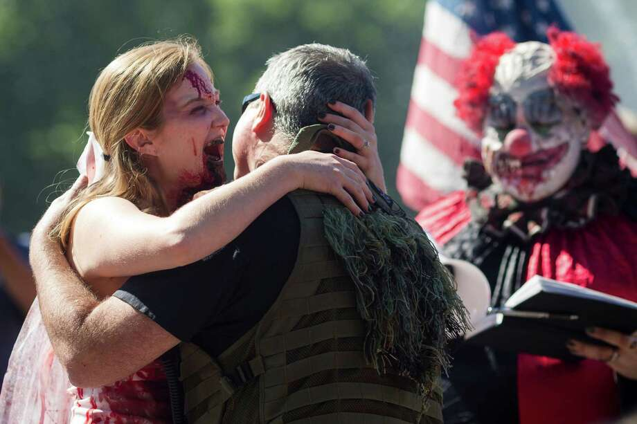 Tiffany O'Brien, left, and John O'Brien, center, kiss after making their wedding vows during the fifth annual Red, White and Dead Zombie Walk Saturday, July 6, 2013, around the Seattle Center in Seattle. This year, the horde relocated from their long-time Fremont location to the larger Seattle Center to accommodate more roaming, undead bodies. Photo: JORDAN STEAD, SEATTLEPI.COM / SEATTLEPI.COM