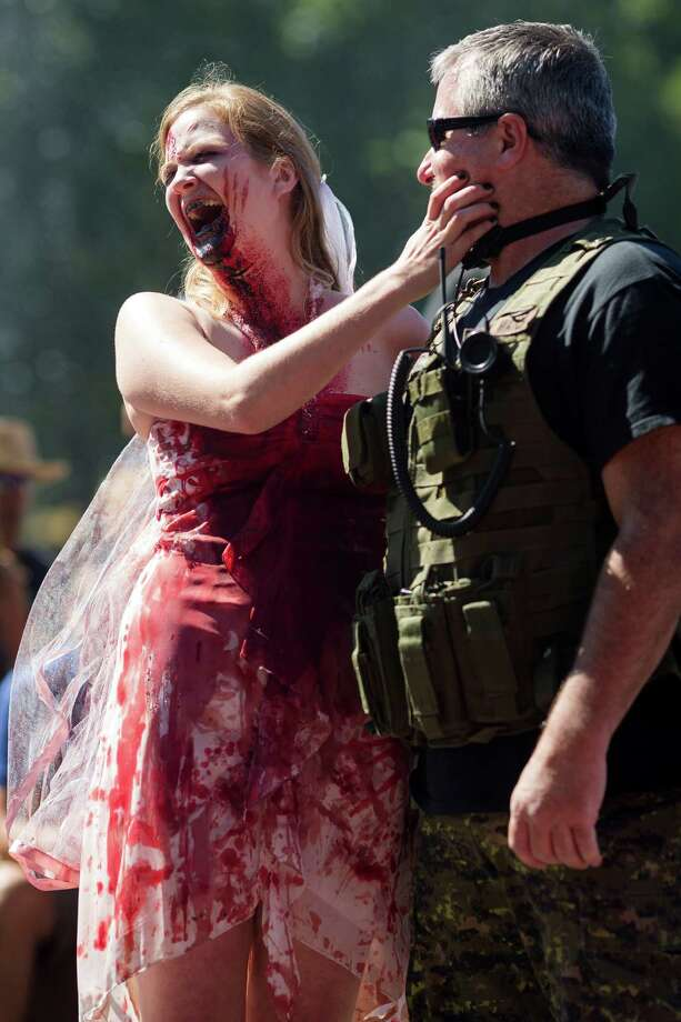 Tiffany O'Brien, left, and John O'Brien, react after making their wedding vows during the fifth annual Red, White and Dead Zombie Walk Saturday, July 6, 2013, around the Seattle Center in Seattle. This year, the horde relocated from their long-time Fremont location to the larger Seattle Center to accommodate more roaming, undead bodies. Photo: JORDAN STEAD, SEATTLEPI.COM / SEATTLEPI.COM