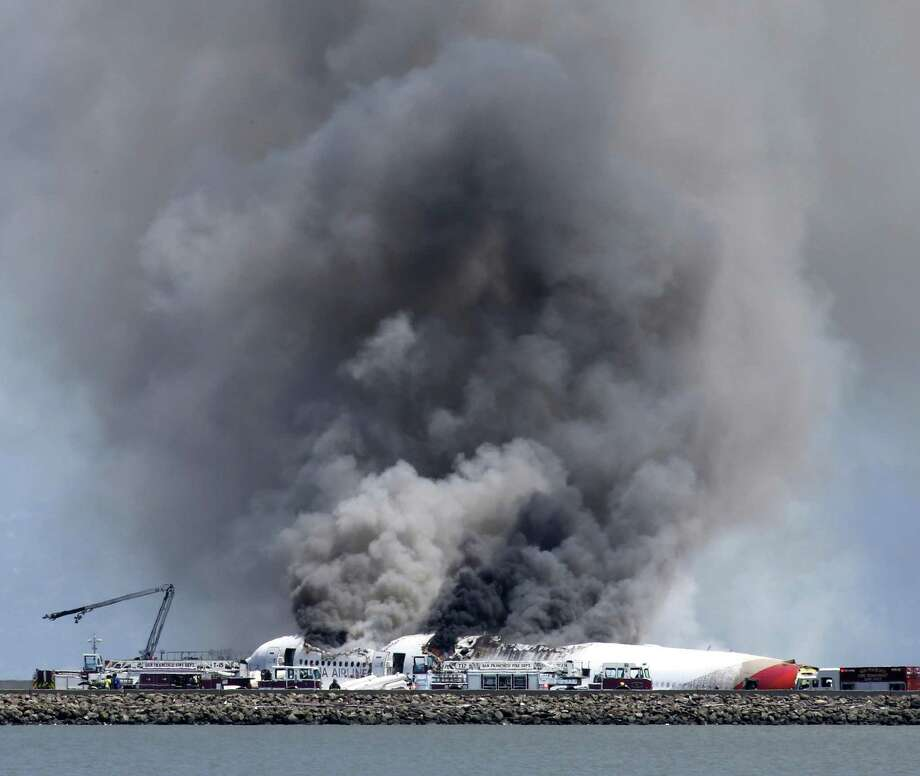 Fire crews surround an Asiana Airlines Boeing 777 after it crashed and broke apart Saturday while landing at San Francisco International Airport. The tail of the plane was sheared off, and spilled fuel caught fire. Photo: JOHN GREEN, MBR / Contra Costa Times