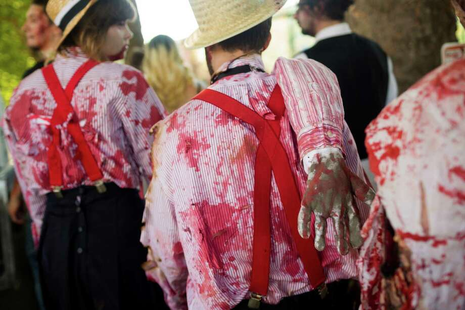 Spattered blood and errant limbs were a popular hit during the fifth annual Red, White and Dead Zombie Walk Saturday, July 6, 2013, around the Seattle Center in Seattle. This year, the horde relocated from their long-time Fremont location to the larger Seattle Center to accommodate more roaming, undead bodies. Photo: JORDAN STEAD, SEATTLEPI.COM / SEATTLEPI.COM